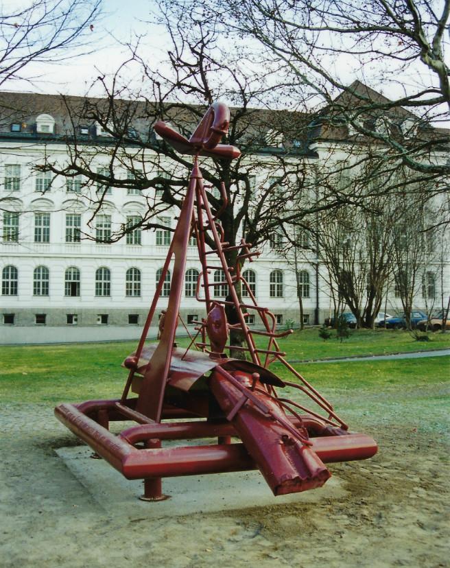Die rote Metallskulptur in einem Park ist das Obdachlosendenkmal von Alois Schild